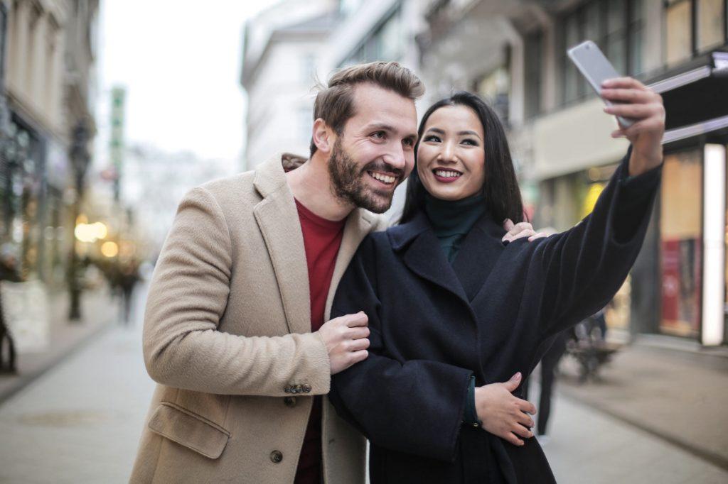 Pärchen strahlt nach professioneller Zahnreinigung in die Handykamera und macht ein hübsches Selfie